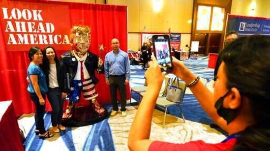 Conference attendees pose for a photo next to a statue of former president Donald Trump at the merchandise show at the CPAC.(AP)