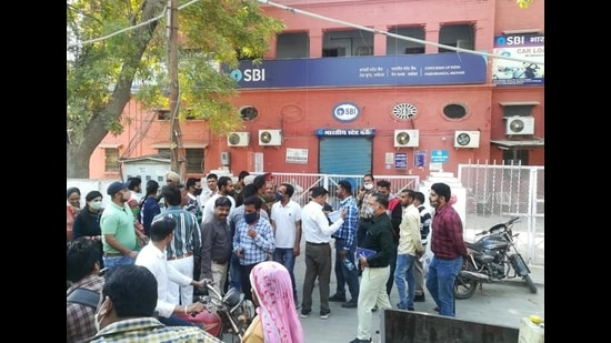 Customers outside the State Bank of India's branch at Bazaar Number 4 in Abohar on Monday after the building was sealed on the local municipal corporation's orders for default on paying rent. (HT Photo)