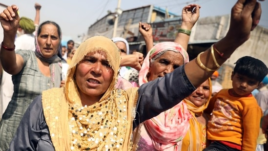 Women farmers raise slogans during a protest against the new farm laws, at the Singhu border in New Delhi