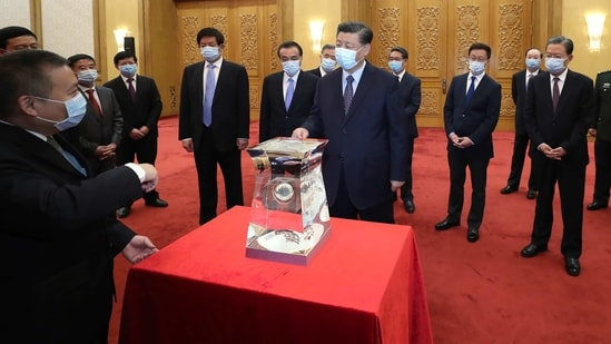 Chinese President Xi Jinping, center, and other Chinese leaders look at a display of lunar samples retrieved from the moon by China's Chang'e 5 lunar lander at the Great Hall of the People in Beijing. (AP)