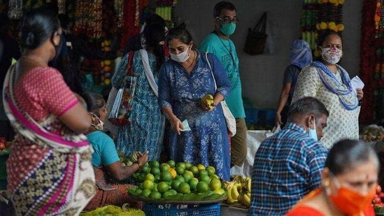 A woman wearing a protective face mask buys fruit in a market, amidst the spread of the coronavirus disease (Covid-19) in Mumbai,. (Reuters Photo)