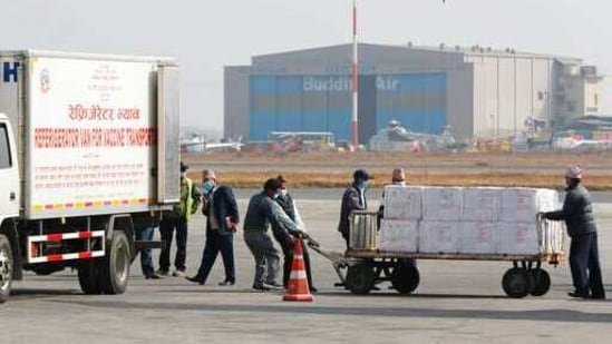 Nepal has also been promised 2.25 million vaccine doses under COVAX. In picture - Nepalese airport ground staffs pull a trolley full of boxes containing AstraZeneca/Oxford University vaccine.(AP)
