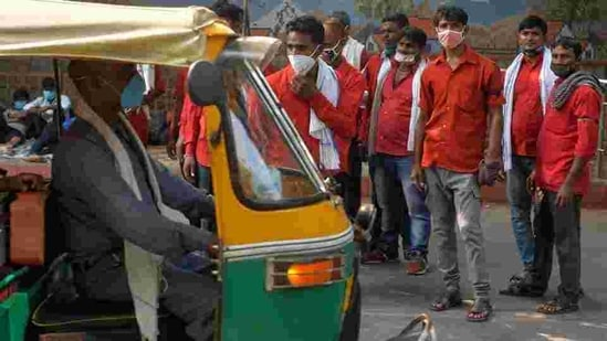 An auto rickshaw moves past coolies wearing face masks outside a railway station.(AP)