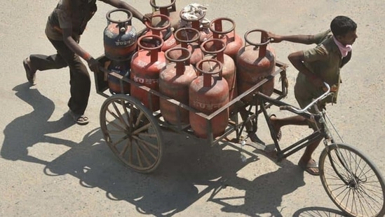 Delivery persons transporting LPG gas cylinders in a rickshaw cart in Patna (Parwaz Khan/HT Photo )