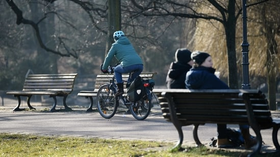 A cyclist drives past people sitting on a park bench at the Volkspark Friedrichshain, amid the coronavirus disease (COVID-19) pandemic, in Berlin, Germany. (REUTERS)