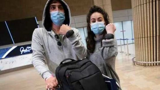 Israeli travellers hold up electronic monitoring bracelets they are required to wear after returning from abroad at the Ben Gurion airport near Tel Aviv, on Monday.(AP Photo)