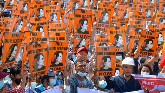Protesters hold posters with the image of detained civilian leader Aung San Suu Kyi during a demonstration against the military coup in Naypyidaw.(AFP)
