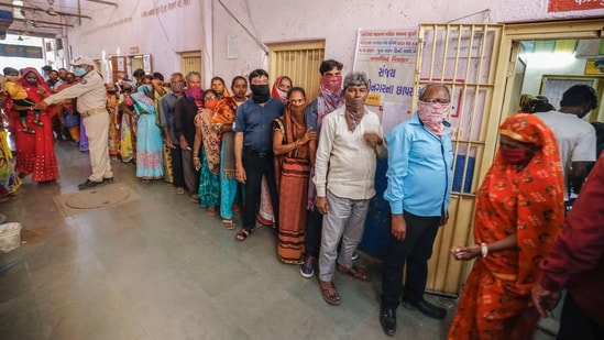 Voters stand in a queue to cast their vote at a polling centre in the first phase of Gujarat civic body elections.