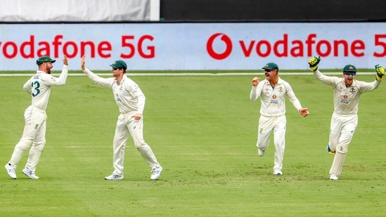Australia's Matthew Wade, left, is congratulated by teammate Steve Smith on a catch to dismiss India's Ajinkya Rahane as David Warner and Tim Paine react during play on day three of the fourth cricket test between India and Australia at the Gabba, Brisbane, Australia.(AP)