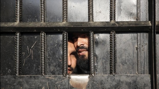 A file photo of Taliban prisoners looking through the door of a prison after an attack in the city of Jalalabad in Afghanistan. (AP)