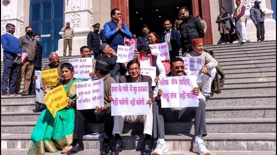 Congress MLAs stage a sit-in at the entrance of the House in Gharsain on Wednesday, March 3. Speaker Premchand Agarwal stands with folded hands) . (Kalyan Das/HT photo)