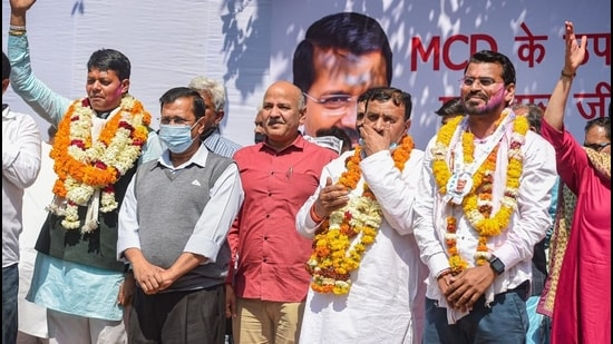 Delhi CM Arvind Kejriwal and deputy CM Manish Sisodia with Aam Aadmi Party (AAP) candidates after emerging victorious in five bypolls to the Municipal Corporation of Delhi, in New Delhi, on March 3. (PTI)