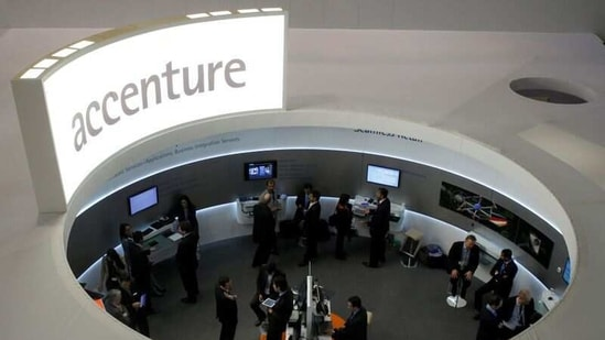 Visitors look at devices at Accenture stand at the Mobile World Congress in Barcelona.(File Photo / REUTERS)