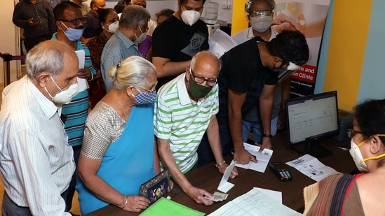 Senior citizens enquiring at the registration desk as they arrive to get the first dose of COVID-19 vaccine during the second phase of the COVID-19 vaccination in Bengaluru on Monday(ANI)