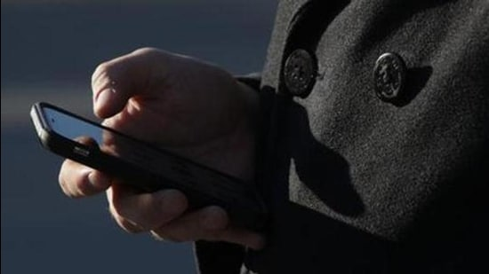 (FILES) In this file photo taken on November 29, 2017, a man checks his cell phone as he waits in line to enter the US Supreme Court to view a hearing in Washington, DC, Carpenter v. United States on whether prosecutors violated the Fourth Amendment by collecting a criminal suspect's cellphone location and movement data without a warrant. In a landmark digital privacy case, the US Supreme Court ruled Friday, June 22, 2018, that police need a warrant before obtaining cell phone location data about a suspect from telecom companies. In a 5-4 decision, the nation's highest court said that cell phone location data is protected under the Fourth Amendment, which guards against unreasonable search and seizure. The case stemmed from the police acquiring mobile phone location information about a robbery suspect without a warrant. / AFP PHOTO / GETTY IMAGES NORTH AMERICA / ALEX WONG (AFP)