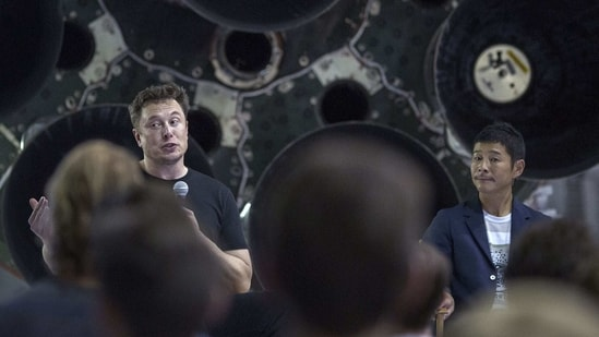 (FILES) This file photo taken on September 17, 2018 shows SpaceX founder Elon Musk (L) and Japanese billionaire Yusaku Maezawa (R) speaking before a Falcon 9 rocket during the announcement that Maezawa will be the first private passenger who will fly around the Moon aboard the SpaceX BFR launch vehicle, at the SpaceX headquarters and rocket factory in Hawthorne, California. - It's the sort of chance that comes along just once in a blue Moon: a Japanese billionaire on March 3, 2021 is throwing open a private lunar expedition to eight participants from around the world. (AFP)