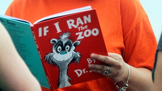 """FILE - In this Sept. 24, 2013, file photo, Courtney Keating, education coordinator of The Literacy Center in Evansville, Ind., reads """"If I Ran the Zoo,"""" By Dr. Seuss, to passersby during an event to promote literacy along the Evansville Riverfront. Dr. Seuss Enterprises, the business that preserves and protects the author and illustrator's legacy, announced on his birthday, Tuesday, March 2, 2021, that it would cease publication of several children's titles including """"And to Think That I Saw It on Mulberry Street"""" and """"If I Ran the Zoo,"""" because of insensitive and racist imagery.(AP)"""