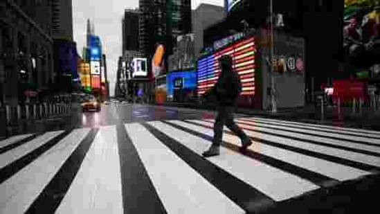 A man crosses the street in a nearly empty Times Square, which is usually very crowded on a weekday morning in New York, March 23, 2020.(AP File Photo )