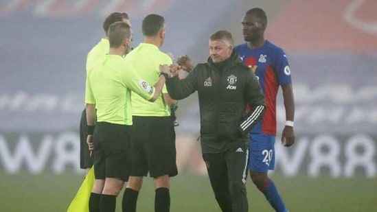 Manchester United manager Ole Gunnar Solskjaer bumps fists with an assistant referee after the match.(Pool via REUTERS)