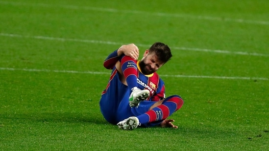 Barcelona's Gerard Pique holds his knee after getting injured during the the Copa del Rey semifinal, second leg, soccer match between FC Barcelona and Sevilla FC at the Camp Nou stadium in Barcelona, Spain, Wednesday March 3, 2021. (AP)