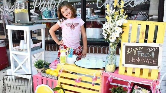 Liza standing at her stand made up of bright pink and yellow wooden crates. (MightyCause.com/Lemonadeforliza)