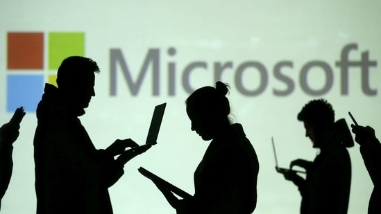 FILE PHOTO: Silhouettes of laptop and mobile device users are seen next to a screen projection of Microsoft logo in this picture illustration taken March 28, 2018. REUTERS/Dado Ruvic/Illustration/File Photo(REUTERS)