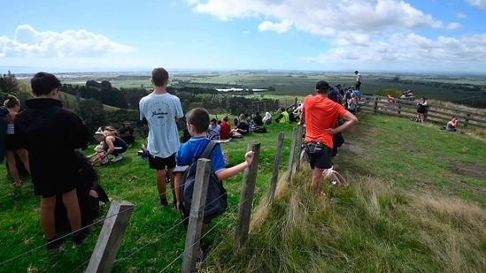 People watch for signs of a tsunami from a hill above Papamoa Beach, New Zealand, as a tsunami warning is issued Friday, March 5, 2021. (AP)
