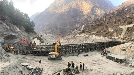 Border Roads Organisation (BRO) workers engaged in building a valley bridge over the Rishi Ganga River at Raini village of the disaster-hit Chamoli district. (PTI)