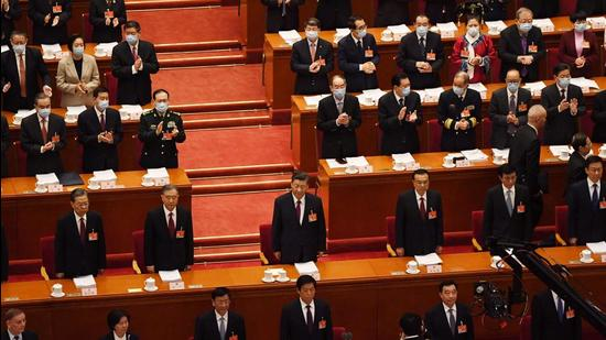 Delegates applaud as Chinese leaders, including President Xi Jinping (centre), arrive for the opening ceremony of the National People's Congress at the Great Hall of the People in Beijing on March 5, 2021. (AFP)