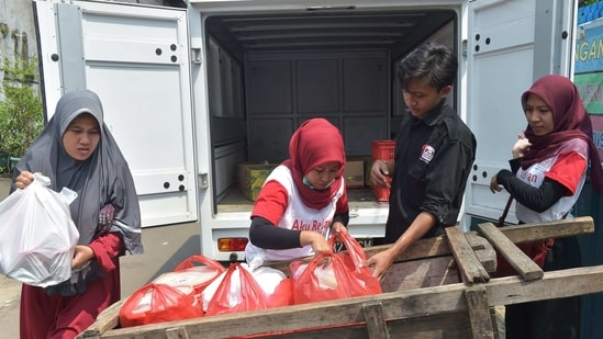 """Volunteers of the programme """"A Blessing to Share"""" unloading uneaten food from a cart for distribution in a slum area in Jakarta in this file picture from 2018. Food Waste Index Report 2021 said that around 931 million tonnes of food waste was generated in 2019, 61% of which came from households, 26% from food service and 13% from retail.(AFP File)"""