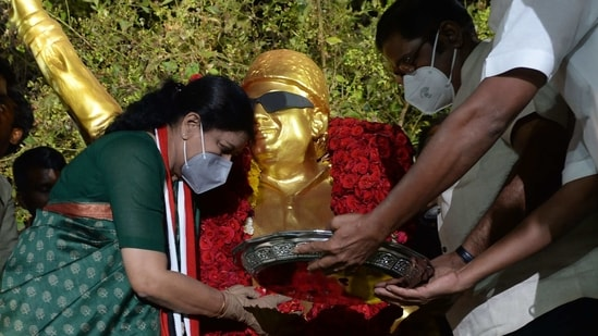 V.K. Sasikala (L), who in 2017 was expelled from her leadership position in the All India Anna Dravida Munnetra Kazhagam (AIADMK) party and recently released from prison after serving a four-year sentence for corruption, pays homage at the statue of AIADMK party founder M.G. Ramachandran in Chennai on February 9, 2021.(AFP)