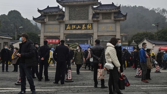 People are seen outside the Biandanshan cemetery in Wuhan, in China's central Hubei province on February 12, 2021, during the first day of the Lunar New Year, which ushers in the Year of the Ox.(AFP)