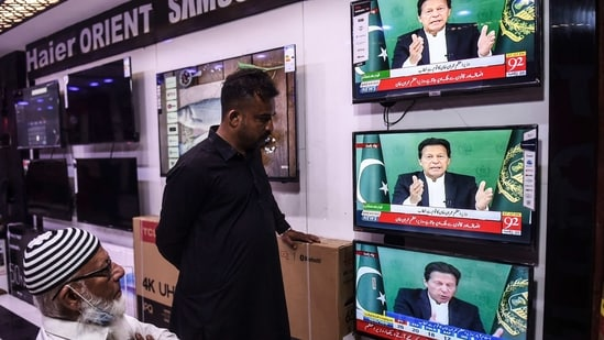 Shopkeepers listen to Pakistan's Prime Minister Imran Khan addressing the nation on television, in Karachi. (AFP. )