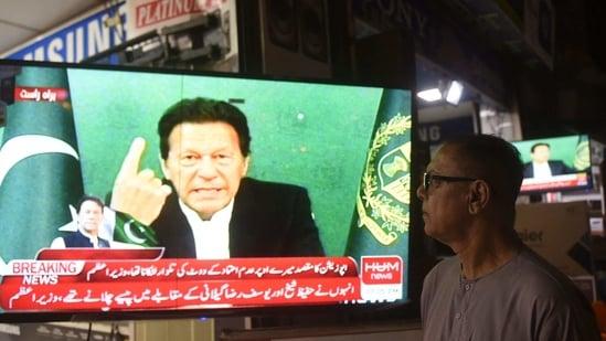 A bystander listens Pakistan's Prime Minister Imran Khan addressing the nation on television. ( AFP)