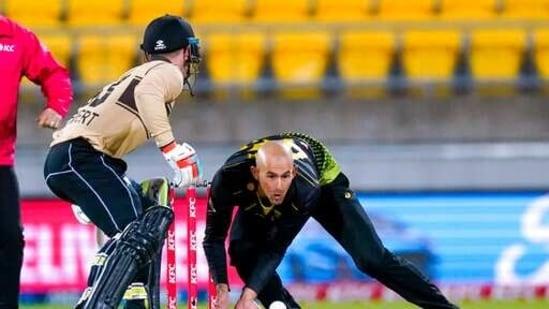 New Zealand's Tim Seifert, left, returns to the crease as Australia's Ashton Agar fields during the 4th T20 cricket international match at Wellington Regional Stadium in Wellington, New Zealand, Friday, March 5, 2021. (AP)