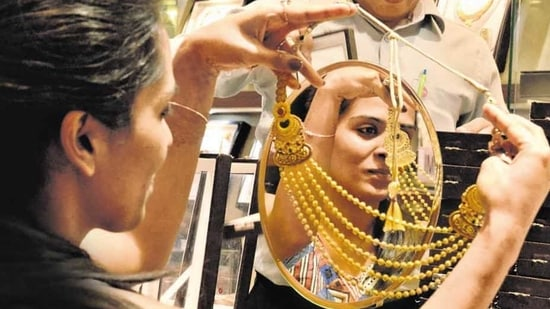 A woman looks at a gold necklace in a shop in Noida in this file photo.(Virendra Singh Gosain/ HT Photo)
