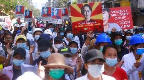 Anti-coup protesters hold up images of deposed leader Aung San Suu Kyi as they gather in Yangon, Myanmar.(AP)