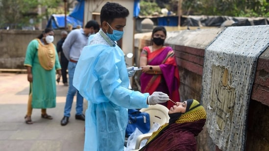 A health worker takes swab sample of a resident for Covid-19 testing in a housing society, amid a surge in coronavirus cases, at Nehru Nagar in Mumbai.(PTI)