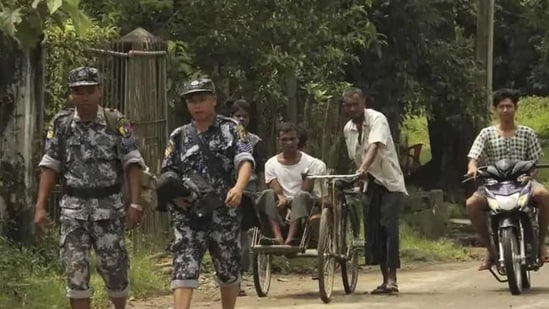 Myanmar Border Guard Police walk ahead of a trishaw driver and passenger along the main road of Buthidaung, northern Rakhine state of Myanmar, on September 6, 2017.(AP file photo for representation purpose)