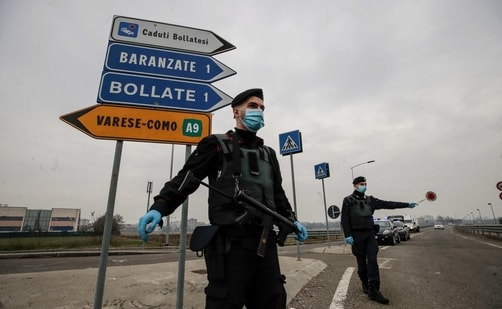Carabinieri officers patrol one of the main access road to Bollate, in the outskirts of Milan, Italy.(AP)