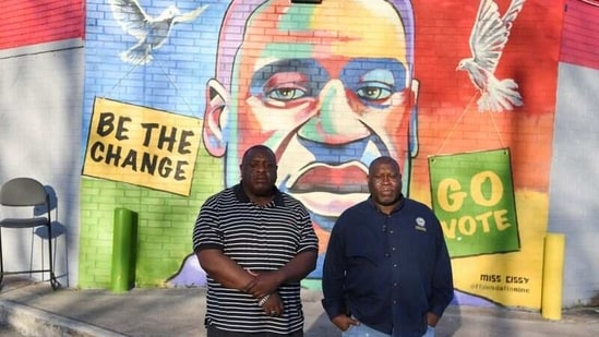 Travis Cains, who grew up in Cuney Homes with George Floyd, and Dexter Brown, Floyd's cousin, pose for a portrait in front of a mural of Floyd.(REUTERS)