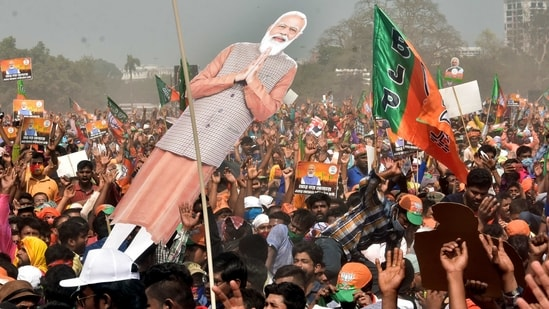 Supporters gather with the flags, posters, and an image of PM Modi during his rally ahead of the West Bengal Assembly Election in the Brigade Parade Ground in Kolkata on Sunday. (ANI Photo)
