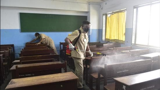 Employees sanitise a classroom. (HT FILE)