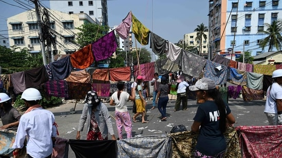Protesters make a barricade across a road with longyi during a demonstration against the military coup in Yangon.(AFP)