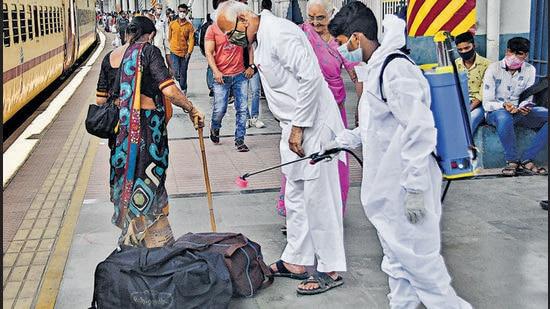 A health worker wearing PPE kit sanitises a luggage of a passenger at Dadar station in Mumbai. (Bhushan Koyande/ HT Photo)