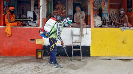 A man wearing a protective mask sprays disinfectant as a preventive measure against the coronavirus disease. (REUTERS)