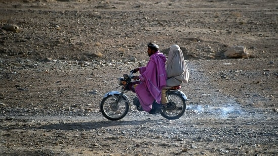 A man rides a motorbike with a woman wearing a burqa sitting behind along a road in the Arghandab district of Kandahar province.(AFP)