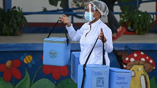 A nurse carries coolers with vials of the Pfizer-BioNTech vaccine against Covid-19 as elderly people are being inoculated.