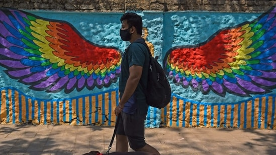 A pedestrian walks past a wall mural in Mumbai on March 6, 2021. (AFP)