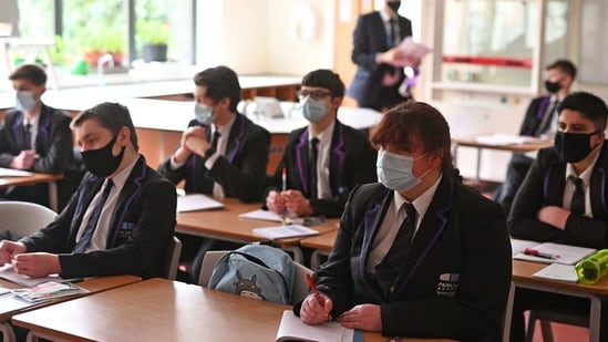 Year 11 students, wearing face coverings, take part in a GCSE science class at Park Lane Academy in Halifax, northwest England on March 8, 2021. (AFP)